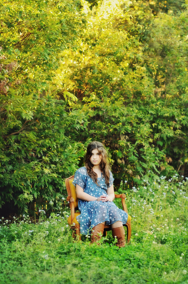 girl in chair in field of clover at Tina Cooper gallery Eumundi