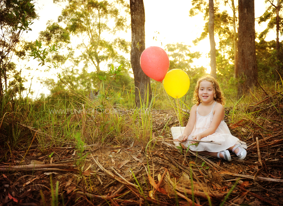 girl in woods with balloons at sunset sunflare