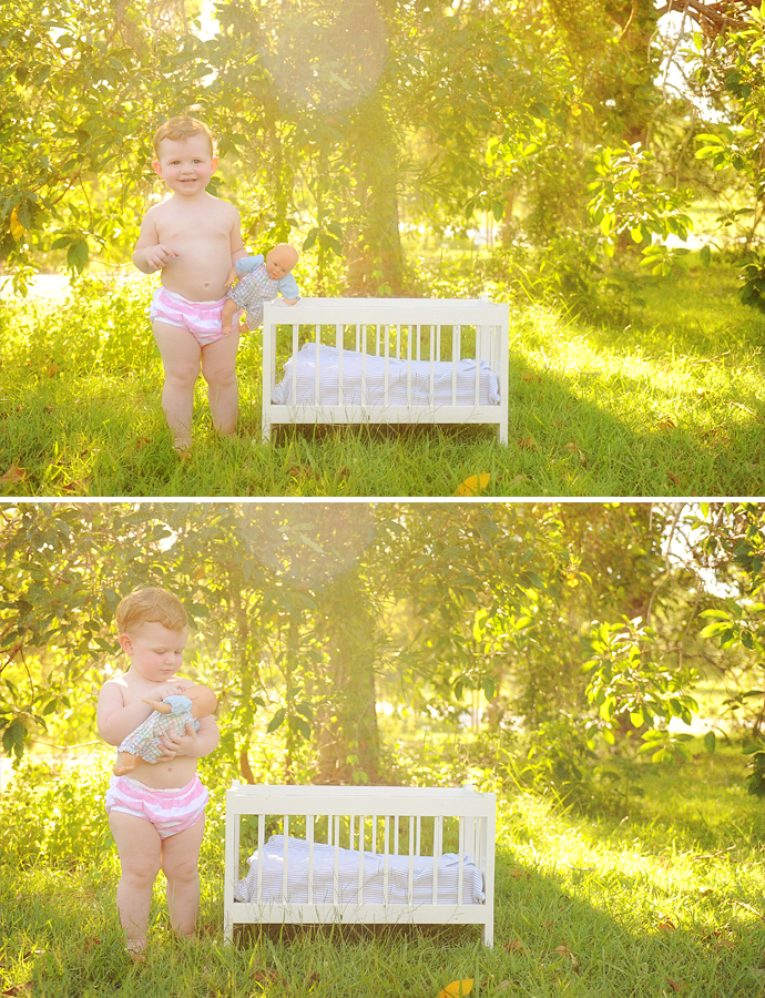 toddler with a baby and cot in a field with sunlight and sunflare
