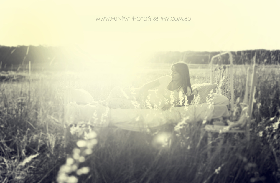 pregnant woman on a bed in a field with sunflare