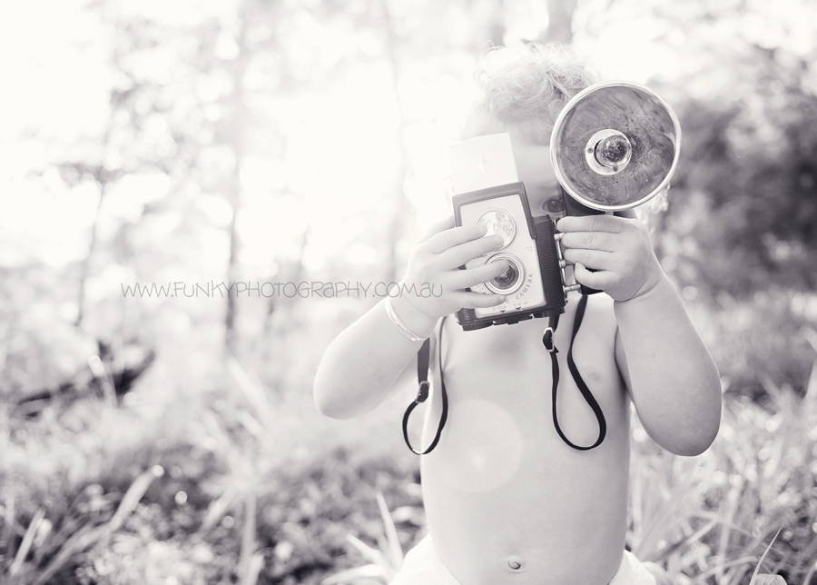 photograph of child with vintage camera and sunflare
