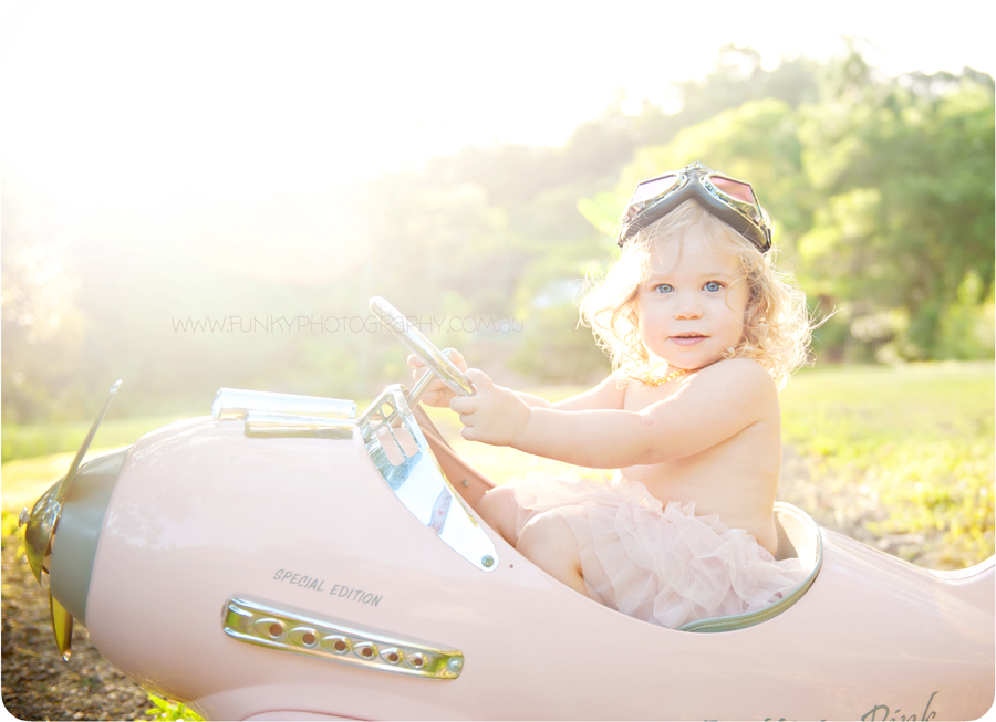 girl toddler in a pink plane vintage in sunlight