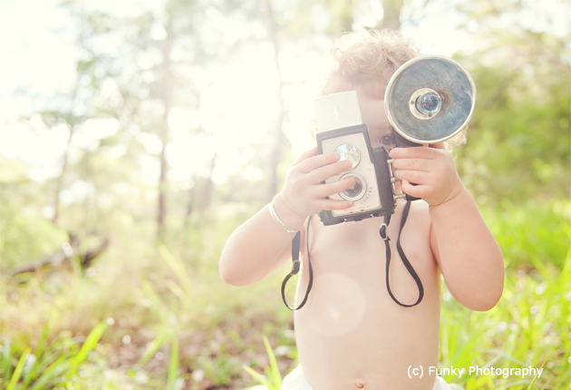 baby with a vintage camera and sunflare