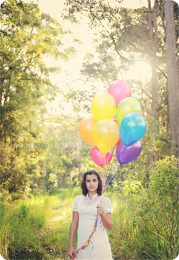 girl with balloons in woods sunflare