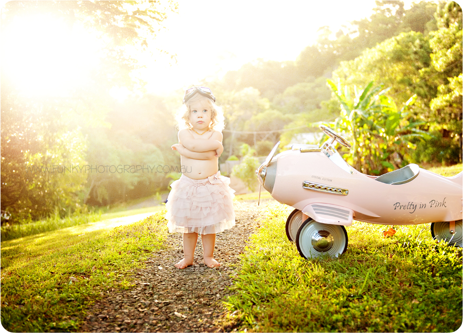 vintage style image of a toddler girl with a pink plane in sunlight with sunflare