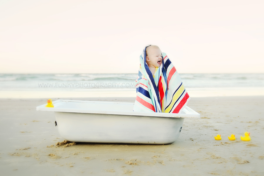 baby in a bath tub on the beach with rubber ducks