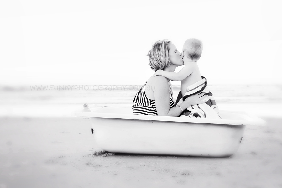 mum and baby kissing in a boat at beach
