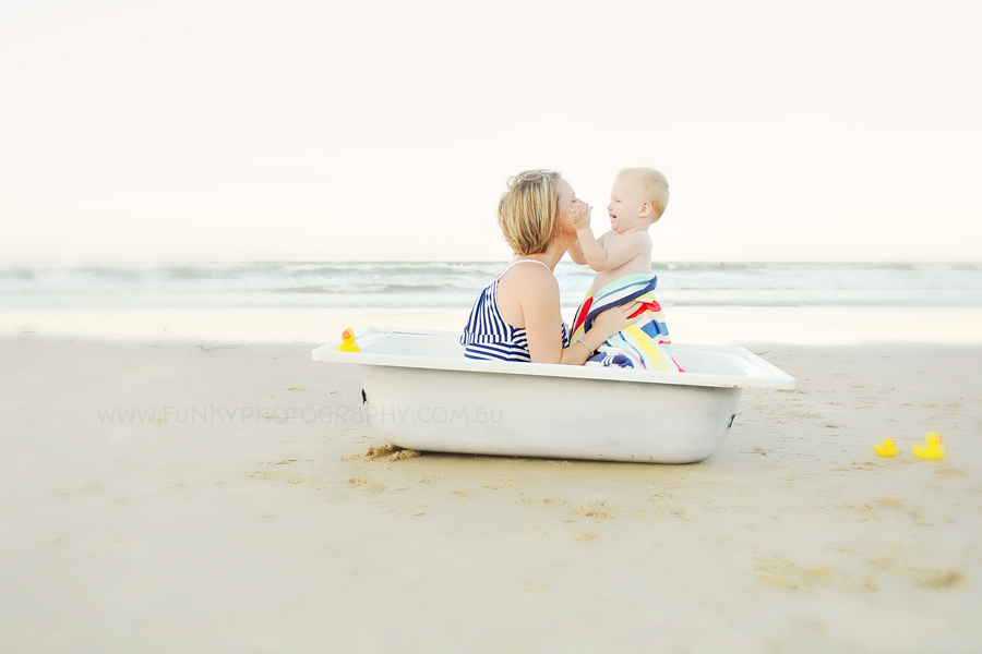 mum and baby in a bath on the beach