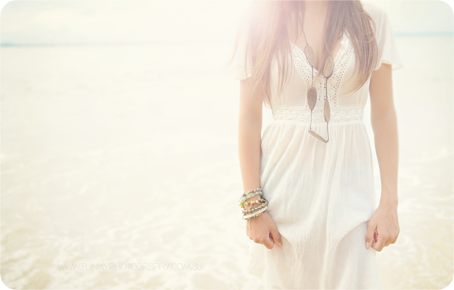 girl standing on noosa beach with sunflare vintage