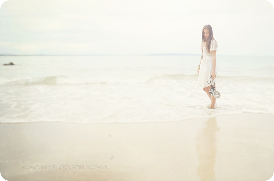 girl walking along beach at little cove with a vintage camera