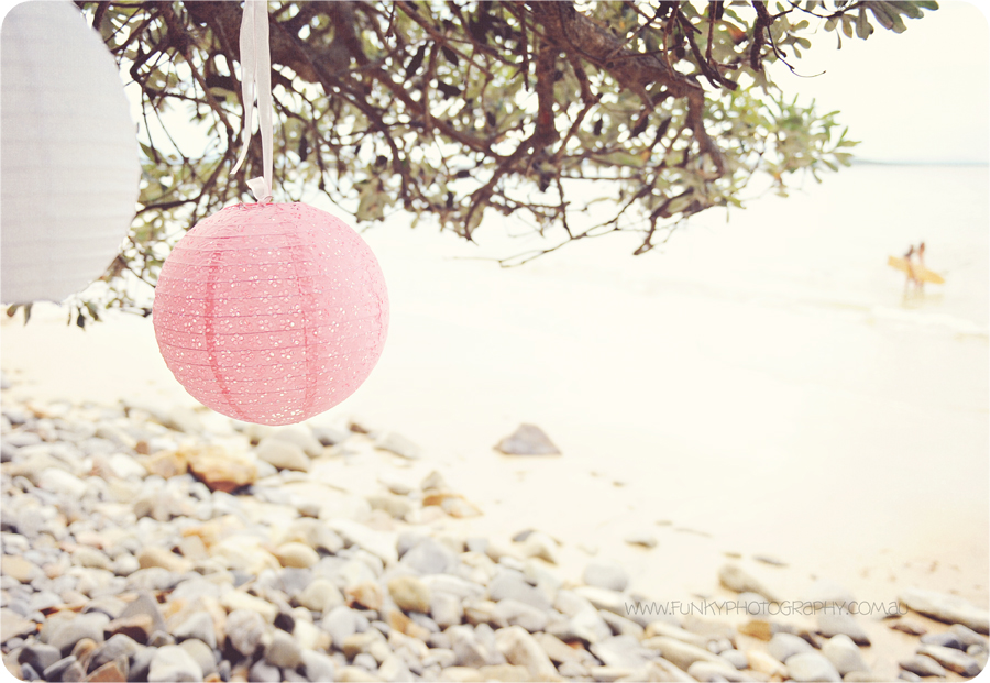 pink and white lanterns hung by ribbons on beach