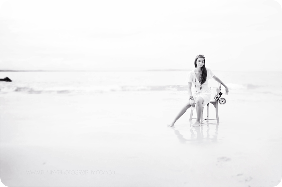 girl sitting on chair on beach with vintage camera
