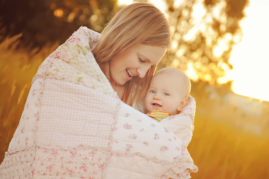 Mum and baby cuddle in a blanket