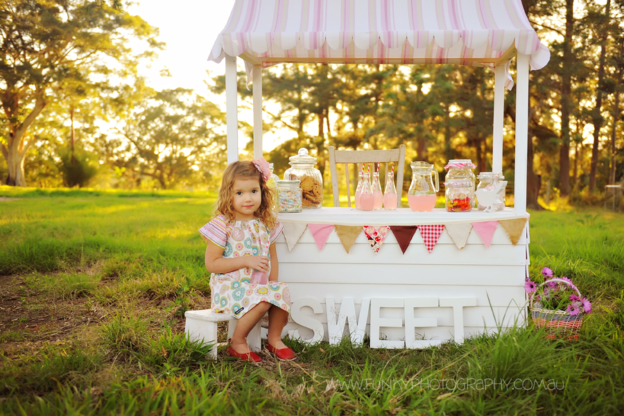 girl sitting drinking pink lemonade at a candy stall