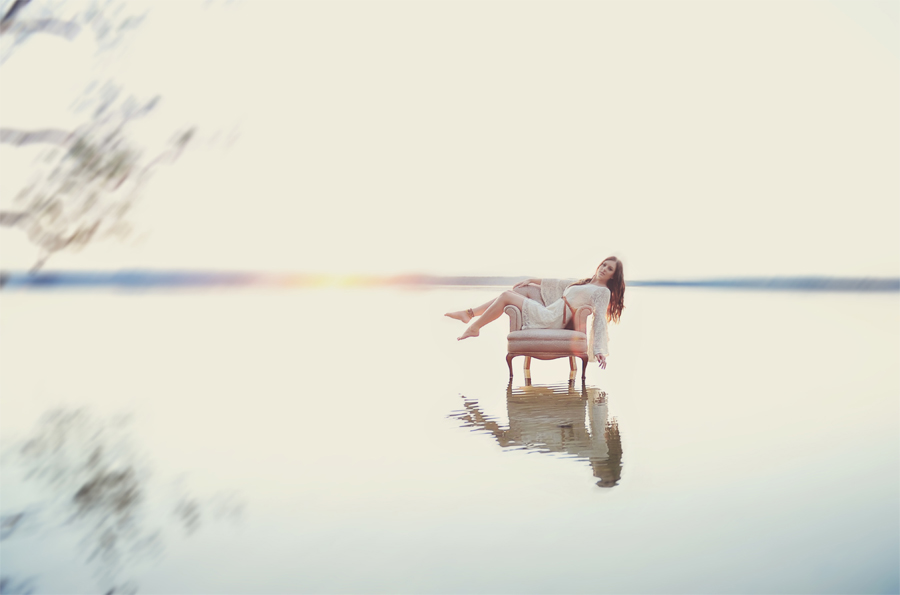 girl on chair in lake at sunrise